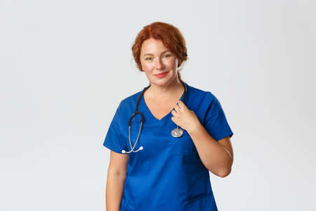 Smiling caring middle-aged redhead doctor, female physician in blue scrubs with stethoscope smiling at camera, treating patients in hospital, testing people for covid-19, standing grey background