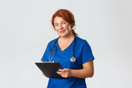 Medicine, healthcare and coronavirus concept. Friendly-looking cute female doctor, physician in scrubs holding clipboard and looking at patient, asking questiones, monitor health, provide checkup