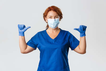Medical workers, covid-19 pandemic, coronavirus concept. Smiling pleasant nurse, female professional doctor in medical mask, gloves and scrubs pointing at herself, being real pro, grey background