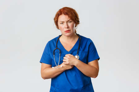 Medicine, healthcare and coronavirus concept. Compassionate redhead female nurse, doctor in scrubs looking with pity, feeling sorry for patient, standing concerned over grey background