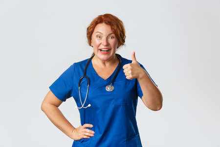 Medicine, healthcare and coronavirus concept. Upbeat redhead middle-aged doctor recommend clinic offer or covid-19 test discount, showing thumbs-up and smiling, approve choice, grey background
