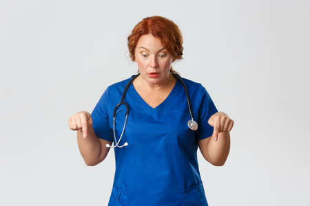 Medicine, healthcare and coronavirus concept. Impressed speechless redhead middle-aged doctor, female nurse in blue scrubs looking and pointing down thrilled, drop jaw and gasping wondered