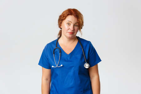 Medicine, healthcare and coronavirus concept. Skeptical and unamused redhead female medical worker, doctor smirk and looking reluctant with dismay, standing in blue scrubs over grey background