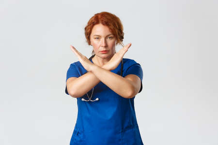 Medicine, healthcare and coronavirus concept. Serious-looking medical worker in scrubs, redhead middle-aged female doctor forbid or disapprove something, show cross stop gesture determined