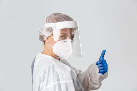 Medical workers, covid-19 pandemic, coronavirus concept. Sassy professional female doctor in personal protective equipment, assure people all under control, showing thumbs-up and smiling