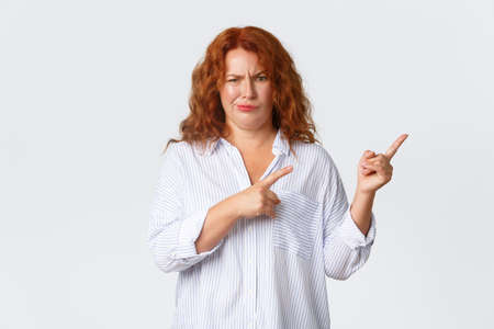 Skeptical and displeased, complaining redhead middle-aged woman smirk unsatisfied, pointing fingers upper right corner with dismay, judging hideous promo banner, standing white background