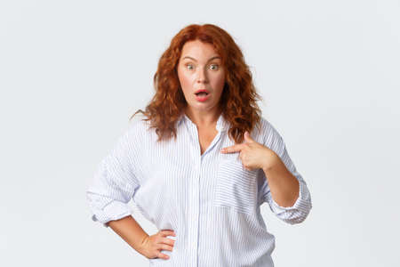 Portrait of shocked and confused redhead woman pointing at herself, drop jaw and stare at camera questioned, being named or chosen unexpectedly, looking surprised, white background
