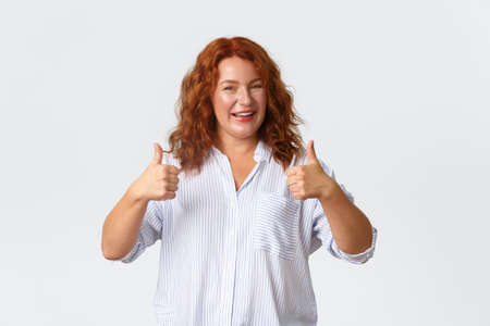 Good job, nice work gesture. Portrait of pleased smiling redhead middle-aged woman encourage you, making compliment, showing thumbs-up in approval, like product, guarantee quality
