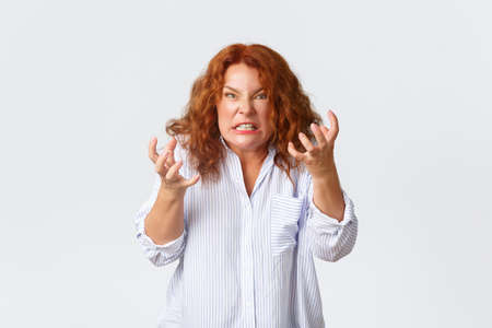 Angry and hateful middle-aged redhead woman looking outraged and bothered, grimacing from hatred, furiously clenching fists as want to kill someone, standing pressured over white background