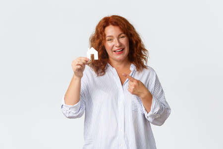 Rent, buying property and real estate concept. Cheerful middle-aged redhead woman becomming home owner, holding small house card and smiling happy, standing white background