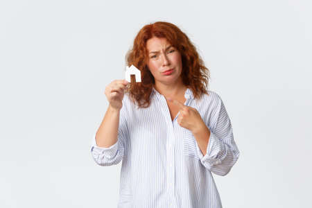 Rent, buying property and real estate concept. Sad middle-aged redhead lady dreaming of having house, pointing at home cardboard and complaining not having money, need loan for buying
