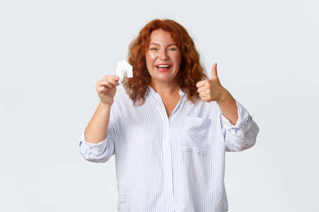 Rent, buying property and real estate concept. Cheerful and pleased middle-aged redhead woman showing house card and thumbs-up as buying new home, receive loan from bank