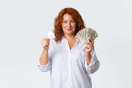 Rent, buying property and real estate concept. Happy middle-aged redhead lady showing money dollars and house card, buying new home, getting loan from bank, standing white background