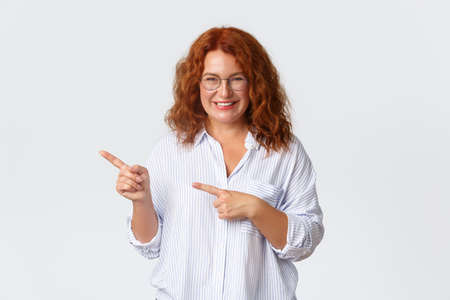 Portrait of smiling pretty middle-aged woman with red hair, wearing glasses, showing way, helping with choice, demonstrate promo banner and looking pleased, standing white background