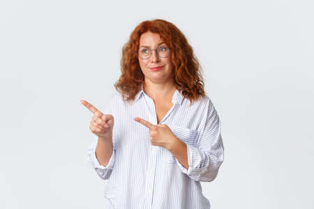 Skeptical and unamused, smirking redhead middle-aged woman looking and pointing at something average, feeling reluctant about promo banner, dont like product, standing white background