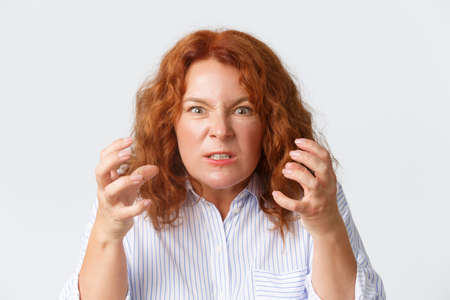 Angry and hateful middle-aged redhead woman looking outraged and bothered, grimacing from hatred, furiously clenching fists as want to strangle someone, cursing over white background Stock Photo