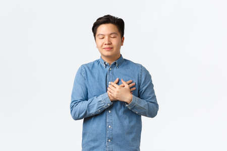 Hopeful dreamy asian man in shirt, close eyes and holding hands on heart, imaging something, feeling love and care, remembering nice memory, thinking about someone, white background