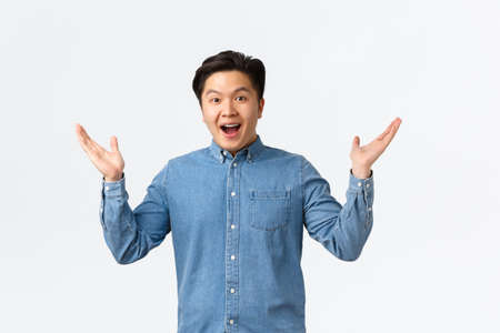 Happy and excited asian surprised guy receive awesome news, raising hands sideways and smiling amazed, praising great job, saying congrats, rejoicing over white background