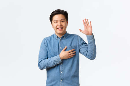 Smiling friendly-looking asian man being honest, raising arm and hold hand over heart while telling truth, making promise or swear something, standing white background sincere