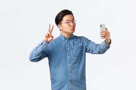 Cute and funny asian young guy pouting silly, taking selfie on smartphone, using photo filter app to change appearance, shooting himself with peace sign and kiss, white background Stock Photo