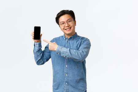 Smiling handsome asian guy with braces and glasses, pointing finger at smartphone screen. Man showing promo or application on mobile phone display, promote site, standing white background