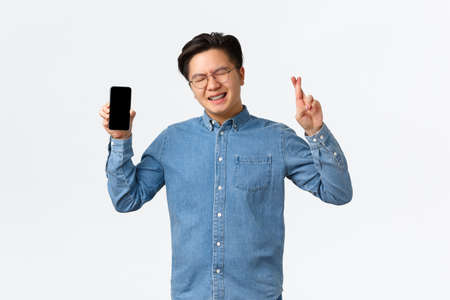 Hopeful asian guy with braces, close eyes and cross fingers good luck, showing smartphone screen, waiting for reply on dating app, begging god, standing white background and making wish
