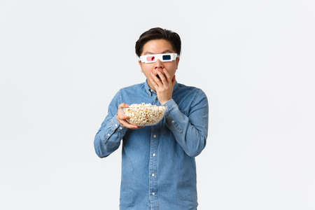 Leisure, lifestyle and people concept. Astonished asian guy in 3d glasses munching popcorn excited looking at TV, watching movie on wide screen, attend cinema, standing white background