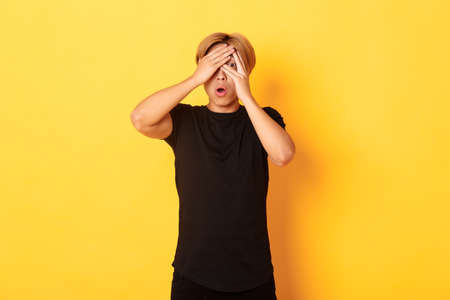 Portrait of embarrassed asian guy with blond hair, gasping startled and shut eyes, peeking through fingers, yellow background