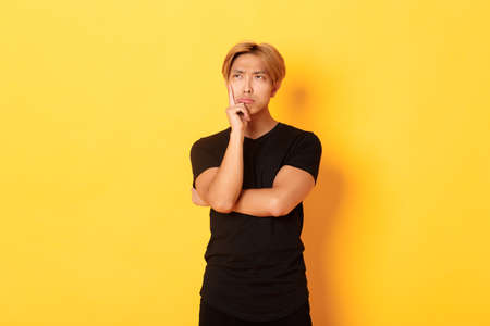Indecisive moody asian guy sulking, looking away thoughtful, standing over yellow background, making decision