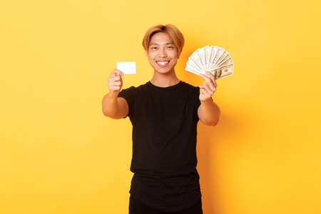 Satisfied attractive korean guy with blond hair, showing money and credit card, smiling happy, yellow background Stock Photo