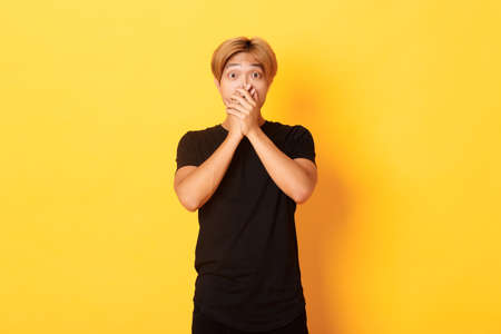 Portrait of surprised gasping asian guy with blond haircut, cover mouth with hands and looking amazed, standing yellow background Imagens