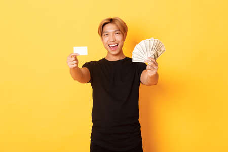 Happy good-looking asian guy in black casual clothes, showing money and credit card, smiling sassy, yellow background