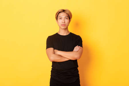 Portrait of serious-looking confident asian guy in black t-shirt, cross arms chest, standing yellow background