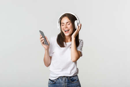 Happy beautiful brunette girl dancing and listening music in wireless headphones, holding smartphone Banque d'images