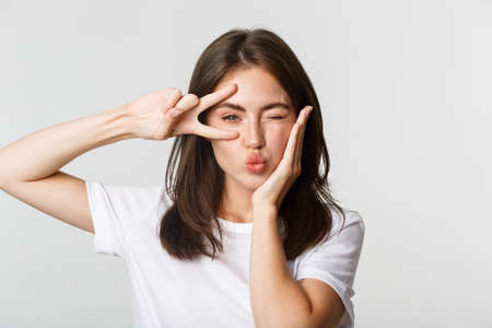 Close-up of happy attractive brunette girl winking silly and showing kawaii peace gesture, white background 版權商用圖片