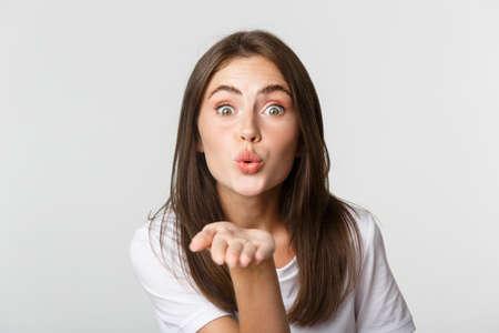 Close-up of beautiful flirty girl pouting lips and sending air kiss at camera