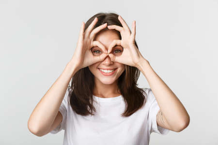 Close-up of happy smiling brunette girl looking through okay gestures, hand glasses, white background 版權商用圖片