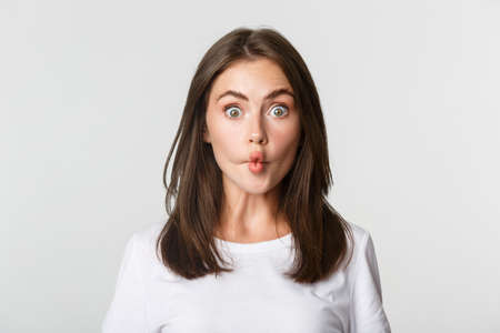 Close-up of funny and cute brunette girl suckink lips, making fish grimace, white background 版權商用圖片