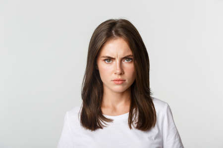 Close-up of pissed-off young girl frowning and looking angry at camera, white background