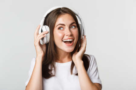 Close-up of beautiful happy girl smiling, enjoying listening music in wireless headphones