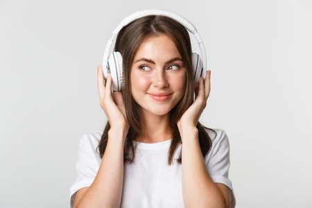 Close-up of smiling attractive brunette girl listening music in headphones, enjoying interesting podcast