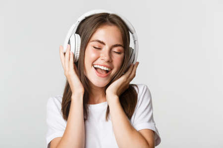 Close-up of attractive happy woman listening music in wireless headphones, singing along