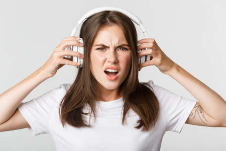 Close-up of angry and confident young girl complaining on awful music in wireless headphones, grimacing