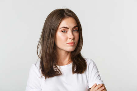 Close-up of attractive brunette girl looking skeptical and unamused