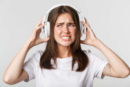 Close-up of annoyed beautiful girl in wireless headphones complaining awful music, grimacing bothered