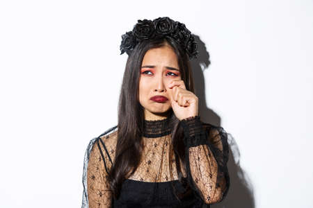 Close-up of young asian woman in witch costume crying and looking miserable, feeling sad, standing over white background