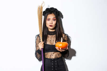Worried and confused asian woman in witch costume looking nervous, holding broom and pumpkin, trick or treating on halloween, standing over white background