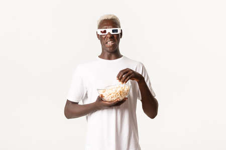 Portrait of disgusted african-american blond guy looking at something unpleasant, cringe from movie, wearing 3d glasses and eating popcorn, white background