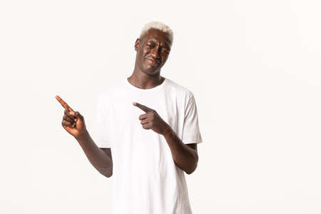 Portrait of skeptical and unamused african-american blond guy, tilt head and grimacing bothered, pointing fingers upper left corner, standing white background Stock Photo