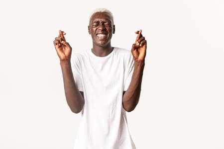 Portrait of begging hopeful african-american blond man, close eyes and cross fingers good luck, making wish, white background